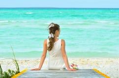 Ein Mädchen in einem Weiß träumt auf dem Pier Stockfotos