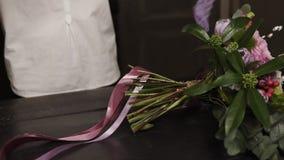 Ein Mädchen in einem weißen Hemd schneidet lange rosa Bänder und purpurrote breite Bänder der Guipurespitze, um einen Blumenstrau stock video footage