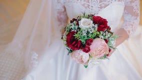 Ein Mädchen in einem weißen Kleid, das einen schönen Blumenstrauß von Blumen hält Abschluss oben feiertag Gute Stimmung stock video footage