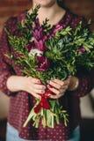 Ein Mädchen in einer Burgunder-Bluse hält einen Blumenstrauß von Tulpen, von Buchsbaum und von Anlagen mit einer Maniküre stockfotos
