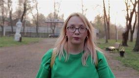 Ein Mädchen in einer grünen Strickjacke geht zum alten Stadt Park am Sonnenuntergang und an den Blicken herum stock video footage