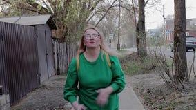 Ein Mädchen in einer grünen Strickjacke läuft fröhlich zur Kamera auf der Straße mit Privathäusern stock video