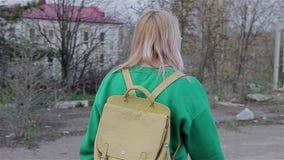 Ein Mädchen in einer grünen Strickjacke mit einem Rucksack hinter ihm ist ein verlassenes Ödland in der Stadt Die Kamera bewegt s stock video