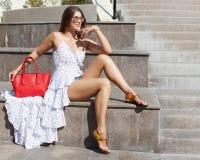 Ein Mädchen in einer hellen Ausstattung mit Sonnenbrille und in einer kühlen großen roten modernen Handtasche an einem heißen Som Stockbild