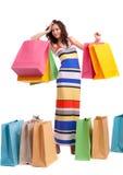 Ein Mädchen in einer langen Kleidfarbe mit Einkaufenbeuteln Stockfotografie