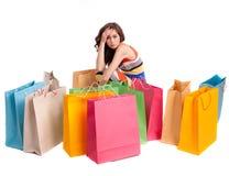 Ein Mädchen in einer langen Kleidfarbe mit Einkaufenbeuteln Stockbild
