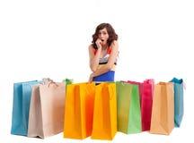 Ein Mädchen in einer langen Kleidfarbe mit Einkaufenbeuteln Stockfotos