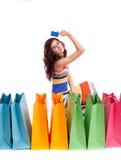 Ein Mädchen in einer langen Kleidfarbe mit Einkaufenbeuteln Lizenzfreie Stockbilder