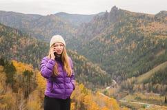 Ein Mädchen in einer lila Jacke sprechend am Telefon in den Bergen, ein Herbstwald mit einem bewölkten Tag Stockfotografie