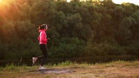 Ein Mädchen in einer rosa Jacke und in schwarzen Hosen läuft nahe dem Fluss in den Kopfhörern, die für den Marathon sich vorberei stock footage