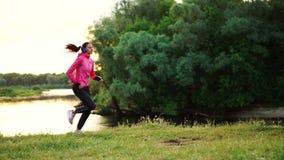 Ein Mädchen in einer rosa Jacke und in schwarzen Hosen läuft nahe dem Fluss in den Kopfhörern, die für den Marathon sich vorberei stock video footage