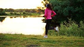 Ein Mädchen in einer rosa Jacke und in schwarzen Hosen läuft nahe dem Fluss in den Kopfhörern, die für den Marathon sich vorberei stock video