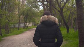 Ein Mädchen in einer warmen schwarzen Jacke geht durch das Holz Das Mädchen geht in Front, die Kamera folgt ihr stock video