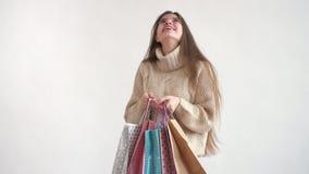 Ein Mädchen in einer warmen Strickjacke öffnet das Paket, untersucht es und lächelnd freut sich stock footage