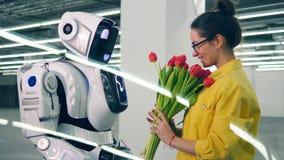 Ein Mädchen empfängt Bündel Tulpen von einem freundlichen Roboter und umarmt es stock video footage