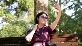Ein Mädchen fotografiert sich telefonisch und sitzt auf einer Bank im Park Junge brunette Frau in der Sonnenbrille und im Kleid stock video footage