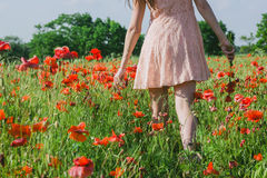 Ein Mädchen geht auf einem Mohnblumengebiet Lizenzfreie Stockbilder