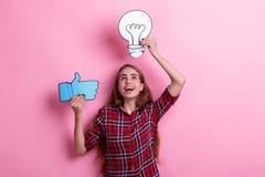 Ein Mädchen, Griffe ein Bild einer Glühlampe und ein Zeichen des Feedbacks greifen oben ab und schauen oben Konzept der Idee Lizenzfreies Stockfoto