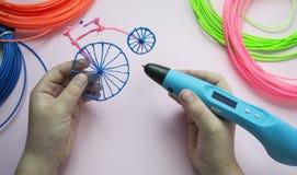 Ein Mädchen hält den Stift 3d und Retro- Fahrrad hergestellt vom Plastik lizenzfreies stockbild