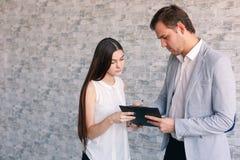 Ein Mädchen hält einen Ordner mit Dokumenten diesen die männlichen Hauptzeichen Lizenzfreie Stockbilder