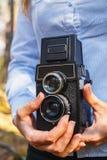 Ein Mädchen hält in ihren Händen einen alten Wald der Filmfoto-Kamera im Frühjahr stockfotos