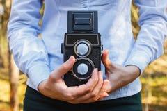 Ein Mädchen hält in ihren Händen einen alten Wald der Filmfoto-Kamera im Frühjahr lizenzfreie stockbilder