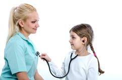 Ein Mädchen hört auf einen Doktor mit einem phonendoscope lizenzfreie stockfotografie
