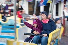 Ein Mädchen hat Spaß mit seiner Mutter in einem Karussell lizenzfreie stockbilder