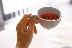 Ein Mädchen holt eine Tasse Tee morgens, Hand mit einer Tasse Tee Lizenzfreie Stockfotos