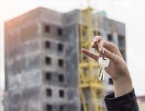 Ein Mädchen in ihrer Hand hält die Schlüssel zu einer Wohnung auf dem Hintergrund einer aufgebauten Haushypothek stockbild