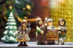 Ein Mädchen im Hintergrund, der Musiker und einen Weihnachtsbaum spielt Lizenzfreies Stockbild