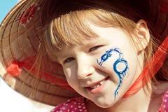Ein Mädchen im Hut mit dem Drachen auf ihrem Gesicht Lizenzfreie Stockfotos