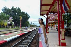 Ein M?dchen im Kleid wartet auf den Zug am Bahnhof Hua Hins stockfotos