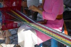 Ein Mädchen im nationalen Kostüm, das an traditionellem hand-spinnendem L arbeitet Stockbild