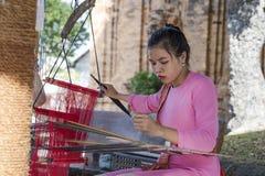 Ein Mädchen im nationalen Kostüm, das an traditionellem hand-spinnendem L arbeitet Lizenzfreie Stockbilder