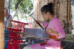Ein Mädchen im nationalen Kostüm, das an traditionellem hand-spinnendem L arbeitet Lizenzfreies Stockbild