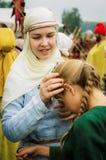 Ein Mädchen im traditionellen slawischen Kostüm zusammen mit seiner kleinen Schwester in der Kaluga-Region von Russland Stockbilder