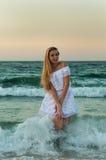 Ein Mädchen im weißen Kleid, das Spaß im Meer hat Stockfotografie