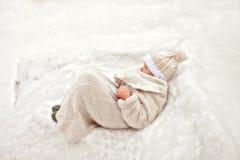 Ein Mädchen im weißen Lügen auf dem Schnee Stockbilder