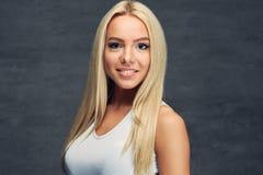 Ein Mädchen im weißen T-Shirt auf grauem Hintergrund Lizenzfreie Stockfotografie
