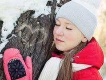 Ein Mädchen im Winter am Baum mit geschlossenen Augen Stockbilder