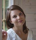 Ein Mädchen ist das Fenster stehendes nahes Lizenzfreie Stockfotos