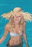 Ein Mädchen ist in einem Swimmingpool entspannend Stockfotografie