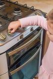 Ein Mädchen, ein Kind schließt einen Gasherd in Abwesenheit von Erwachsenen, t mit ein stockbild