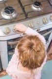 Ein Mädchen, ein Kind schließt einen Gasherd in Abwesenheit von Erwachsenen, t mit ein lizenzfreies stockfoto