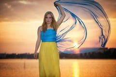 Ein Mädchen kleidete im gelben blauen Kleid im Sonnenuntergang an Stockfotografie
