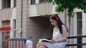 Ein Mädchen liest ein Buch im Park, beim Rauchen und fängt an zu gähnen stock footage
