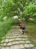 Ein Mädchen macht Fotos auf den Kameraweinleseschritten im grünen Park stockfotos