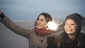 Ein Mädchen mit Bengal-Lichtern hat Spaß Eine Partei auf dem Strand mit Bengal-Feuer stock video footage