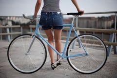 Ein Mädchen mit blauem Fahrrad stockbild